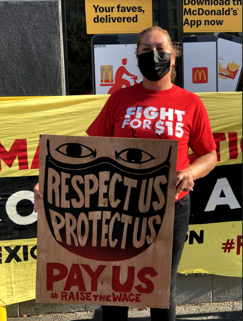 McDonald's worker Maria Ruiz stands in front of a McDonald's location in West Oakland, CA at the Fight for 15 car caravan on Friday, January 15, 2021.