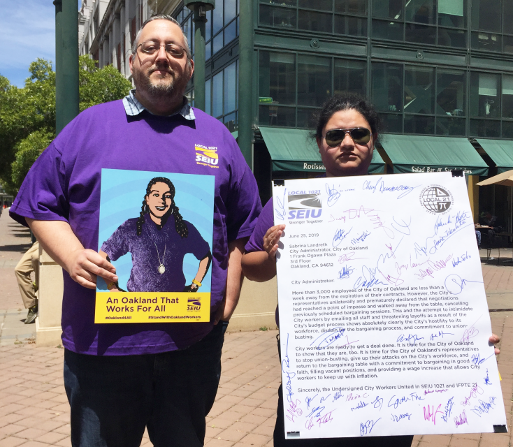 Two proud City of Oakland workers hold an SEIU 1021 poster and the letter our members delivered to Sabrina Landreth.